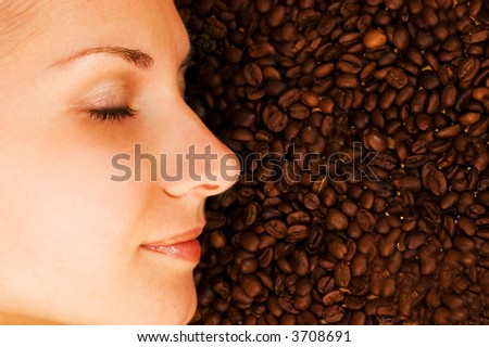 Beautiful girl's face on over coffee bean background - stock photo