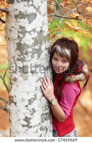 Beautiful girl's portrait near tree in the autumn park - stock photo