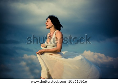 Beautiful girl screaming on the background of beautiful cloudy sky - stock photo