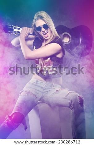 beautiful girl screaming wirh a guitar - stock photo