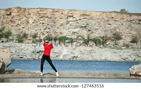 Beautiful girl sexy blonde girl engaged in fitness on the lake - stock photo