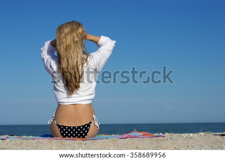Beautiful girl sexy blonde girl posing on the beach by the sea