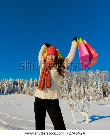 Beautiful Girl Shopping and Snow Covered Trees - stock photo