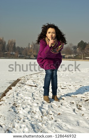 Beautiful girl shows a sign to keep quiet - stock photo