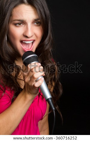 Beautiful girl singing with microphone - stock photo