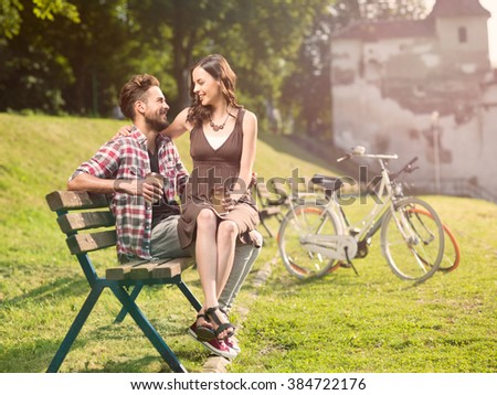 beautiful girl sits in the arms of smiling handsome friend with a coffee in hand and bicycles in the background - stock photo