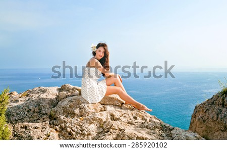 Beautiful girl sits on a hill on a background of the sea