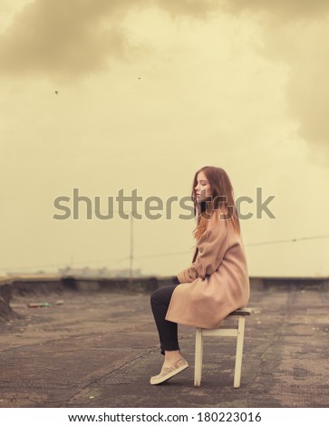 beautiful girl sits on an old roof - stock photo