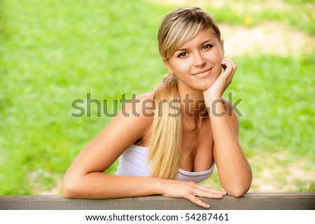 Beautiful girl sits on bench against summer nature.