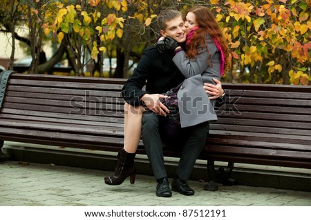 beautiful girl sits on her boyfriend knees in park bench