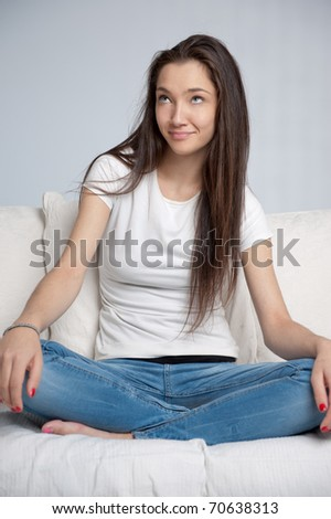 Beautiful girl sitting at home with a dreamy expression - stock photo