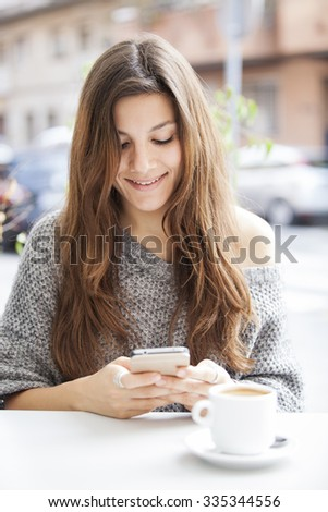 Beautiful girl sitting in a terrace bar and smiling while holding cell phone