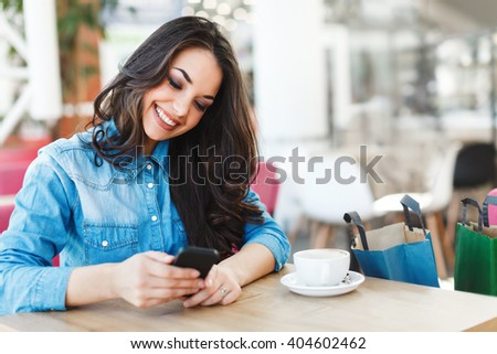 Beautiful girl sitting in cafe in shopping mall, looking at phone and smiling, holding it with both hands. Head turned left a little bit. Colorful shopping bags standing near her on chair. - stock photo