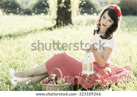 Beautiful girl sitting in the grass. On nature - stock photo