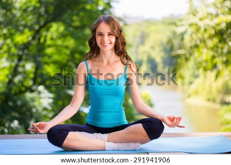 Beautiful girl sitting in the lotus position. Meditation. - stock photo
