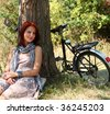 Beautiful girl sitting near bike and tree at rest in forest. - stock photo