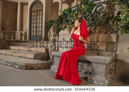 Beautiful girl sitting on a bench in the interior of an old castle - stock photo
