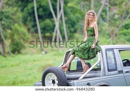 Beautiful girl sitting on a car - stock photo