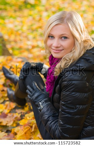 Beautiful girl sitting on a rock, autumn color leaves on the background - stock photo