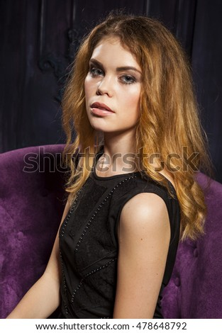 Beautiful girl sitting on a soft violet chair