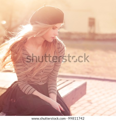 Beautiful girl sitting on a warm sunny day - stock photo