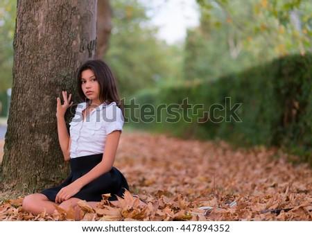 Beautiful girl sitting on autumn leaves - stock photo