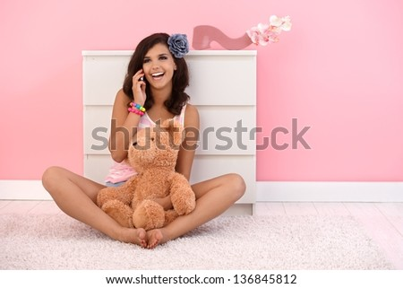 Beautiful girl sitting on floor with teddy bear, talking on mobile phone. - stock photo