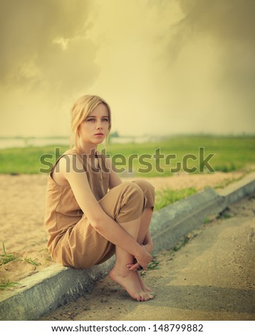 beautiful girl sitting on the edge of the road - stock photo