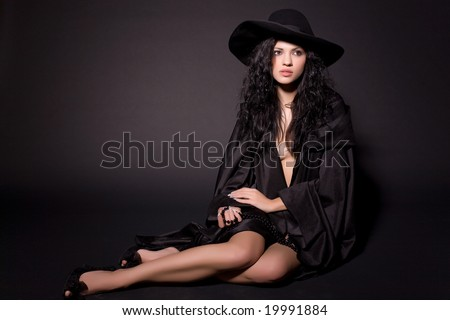 Beautiful girl sitting on the floor, isolated on black background