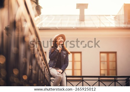 beautiful girl sitting on the railing of a hat backlight. spring sunset - stock photo