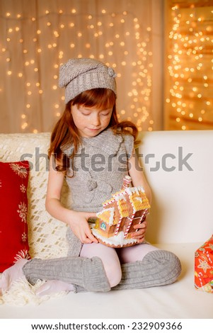 Beautiful girl sitting on the sofa with a gingerbread house - stock photo
