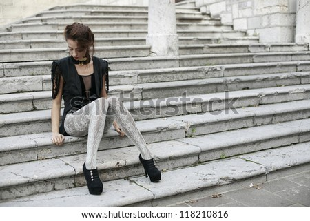 beautiful girl sitting on the stairs - stock photo