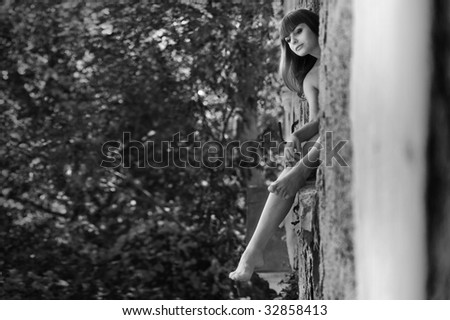 beautiful girl sitting on the window looking outside - stock photo