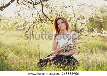 Beautiful girl sitting with a white bouquet in the lush spring garden