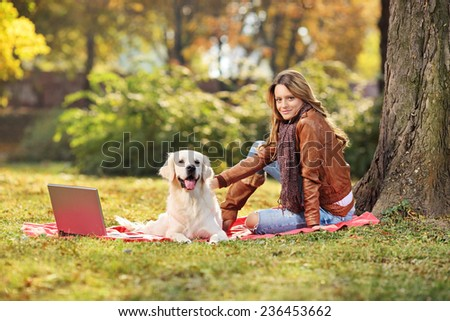 Beautiful girl sitting with her dog in park on blanket - stock photo