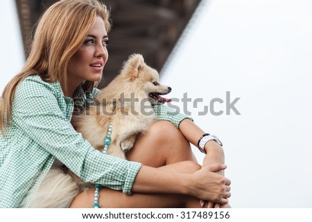 beautiful girl sitting with her little cute dog  - stock photo