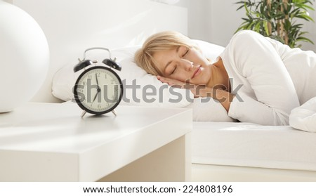 beautiful girl sleeping in her bed. clock on the nightstand. focus on face - stock photo