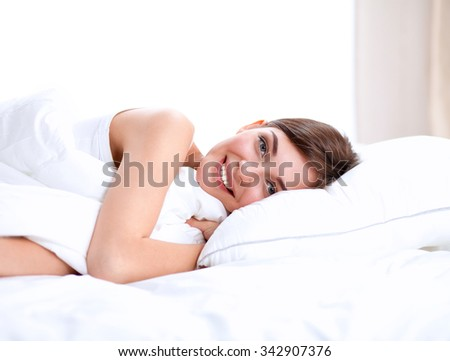 Beautiful girl sleeps in the bedroom, lying on bed