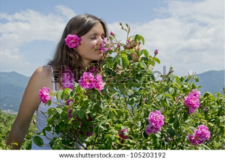 Beautiful girl smelling a rose in a field of roses - stock photo