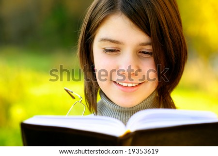 Beautiful girl smiles and looks in book, close up. - stock photo