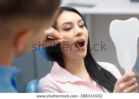 Beautiful girl smiles and looks in the mirror dental clinic - stock photo
