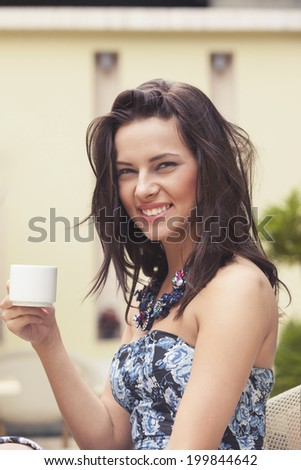 Beautiful girl smiling and drinking coffee - stock photo