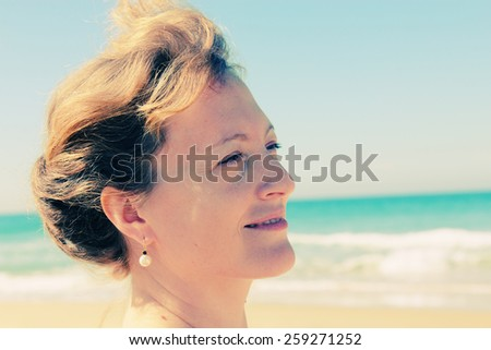 Beautiful girl smiling on the beach with the sand, sea and blue sky in the background - stock photo