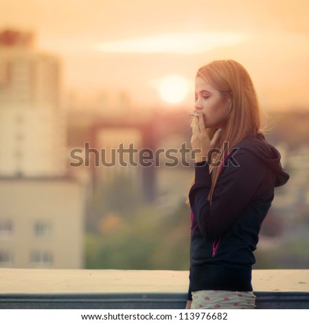 beautiful girl smokes on the roof - stock photo