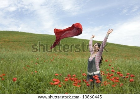 Beautiful girl standing among red poppies and launching a red scarf