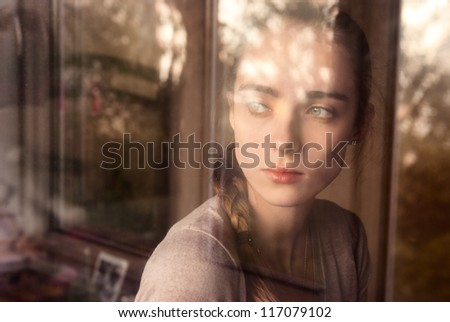 Beautiful girl standing at the window watching - stock photo