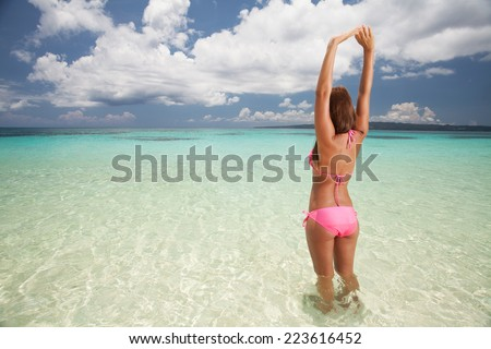 Beautiful girl standing in water at exotic beach - stock photo