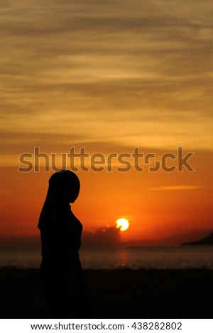 beautiful girl standing on beach at sea at the sunrise