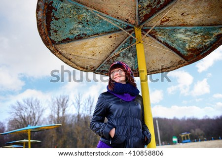 Beautiful girl standing under an umbrella on the beach in autumn - stock photo