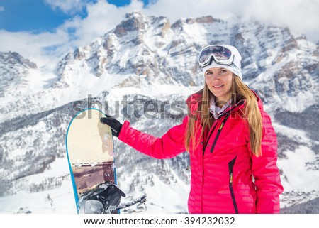 Beautiful girl standing with a snowboard in a pink jacket with the mountain background